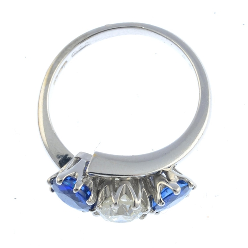 47 - An 18ct gold sapphire and diamond three-stone ring. The brilliant-cut diamond, with circular-shape s...