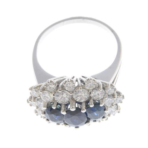48 - A sapphire and diamond cluster ring. The oval-shape sapphire line, with brilliant-cut diamond double...