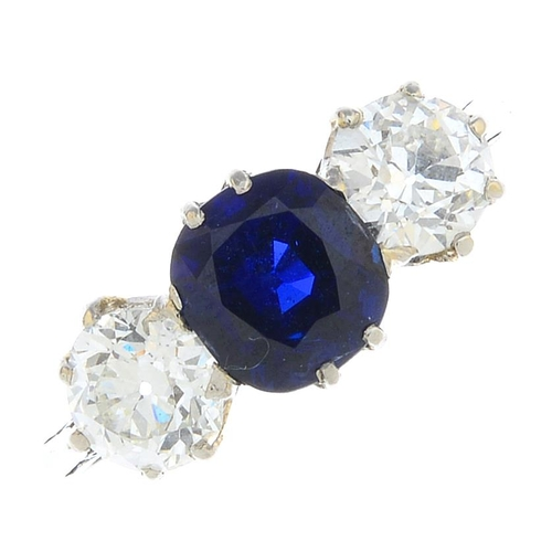 55 - A sapphire and diamond three-stone ring. The cushion-shape sapphire, with old-cut diamond sides and ...
