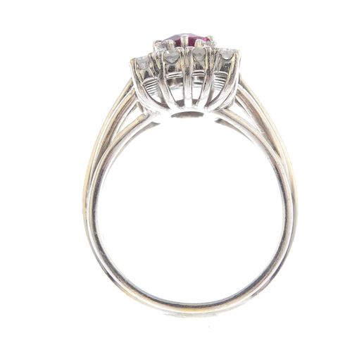 58 - A ruby and diamond cluster ring. Of rectangular outline, the oval-shape ruby, with single-cut diamon...