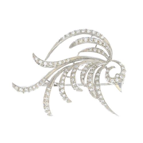 59 - A mid 20th century diamond brooch. Designed as a pave-set diamond stylised bird in flight, with poli...