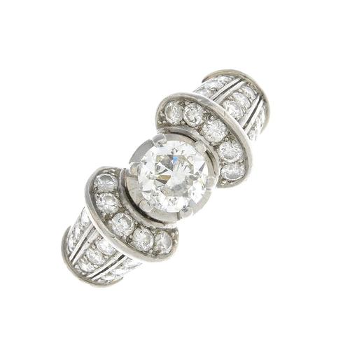 60 - A mid 20th century platinum diamond dress ring. The brilliant-cut diamond, with similarly-cut diamon...