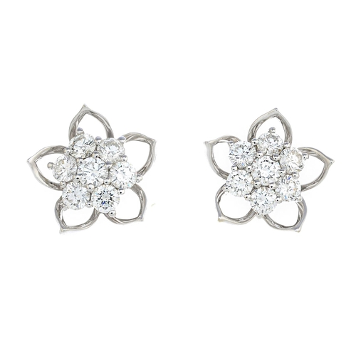 7 - A pair of diamond earrings. Each designed as a brilliant-cut diamond floral cluster, with openwork p...
