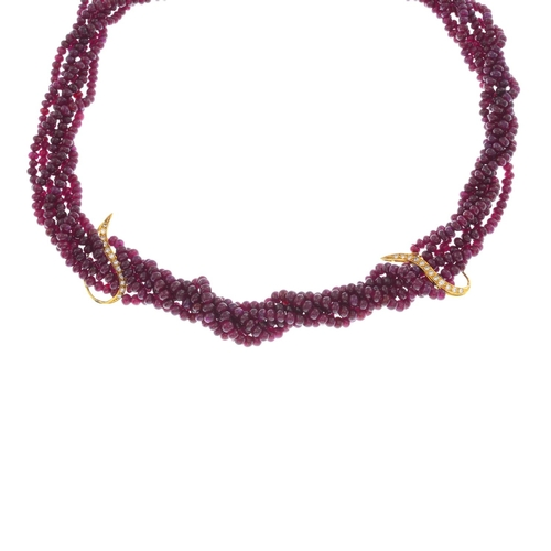 9 - ASPREY & CO. - an 18ct gold diamond and ruby necklace. Designed as a series of intertwined ruby stra...