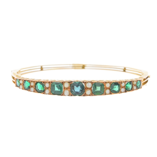 7 - A late Victorian 9ct gold paste and split pearl hinged bangle. The graduated cushion-shape green pas...