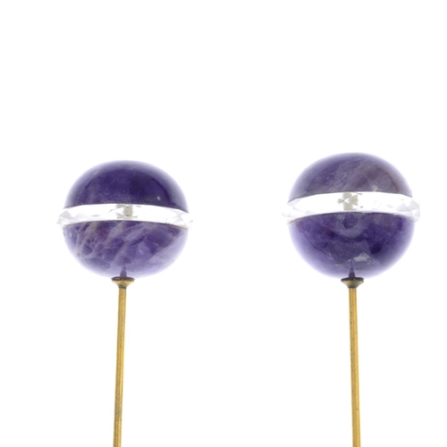 13 - A pair of early 20th century amethyst and rock crystal hatpins. Each designed as an amethyst sphere,...