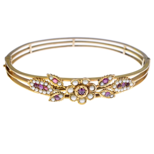 3 - A ruby and split pearl hinged bangle. Designed as a circular-shape ruby and split pearl floral clust...