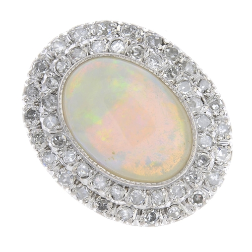 39 - An opal and diamond cluster ring. The oval opal cabochon, with single-cut diamond double surround. E...