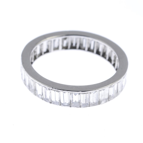 42 - A diamond full eternity ring. The baguette-cut diamond line, within a channel setting. Estimated tot...