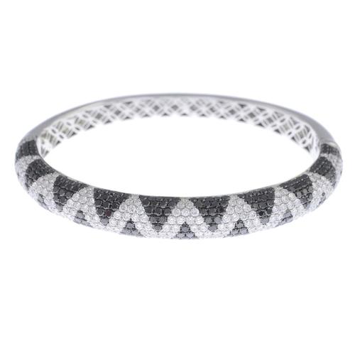 43 - An 18ct gold diamond and gem-set hinged bangle. The brilliant-cut diamond zig-zag line, with pave-se...