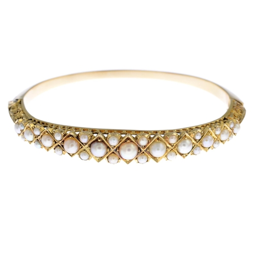 5 - A split pearl hinged bangle. The graduated split pearl half-bangle, with geometric mount and scrolli...