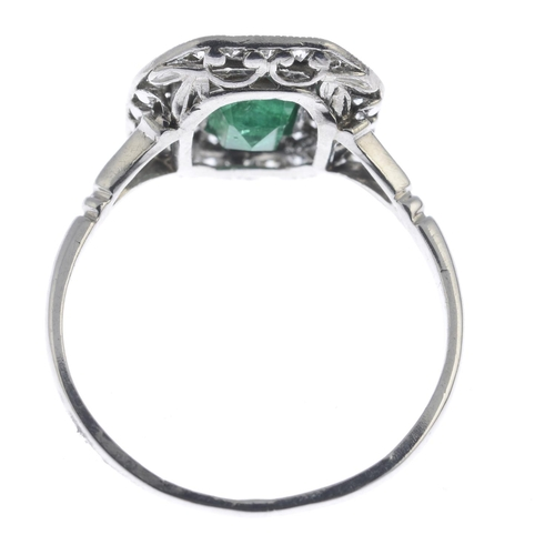52 - An emerald and diamond cluster ring. The rectangular-shape emerald, with single-cut diamond double s...