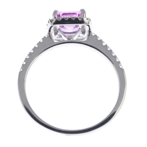 54 - A sapphire and diamond cluster ring. The rectangular-shape pink sapphire, with brilliant-cut diamond...