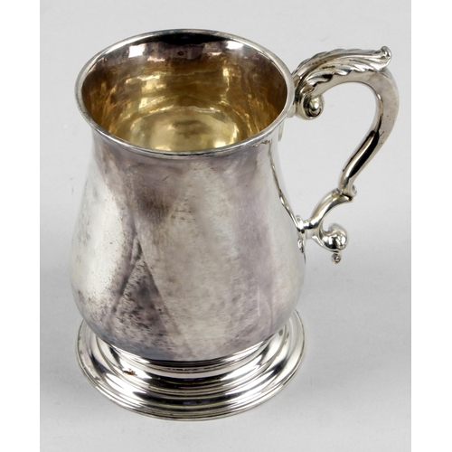 23 - A George II plain silver pint mug, of baluster form to a flared footed base, with acanthus capped do...
