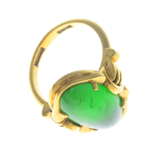 10 - A jade ring. The oval jadeite cabochon, with grooved scroll surround and geometric shoulders. Verbal...