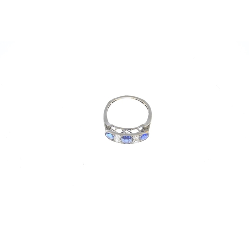 12 - An early 20th century platinum sapphire and diamond ring. The graduated cushion-shape sapphire three...