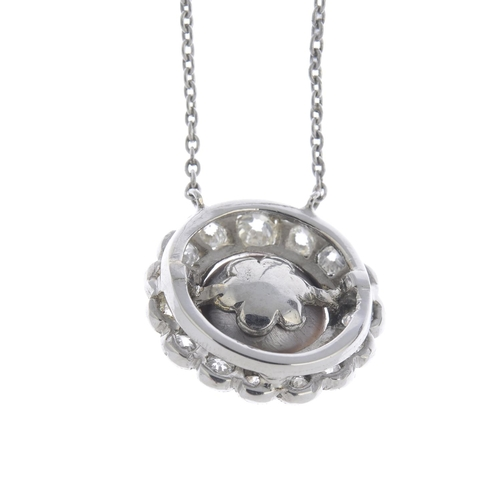 21 - A natural pearl and diamond cluster pendant. The black pearl, measuring approximately 11.1 by 10.9 b...