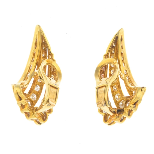 26 - A pair of diamond earrings. Each designed as a brilliant-cut diamond three-row curved chevron, with ...
