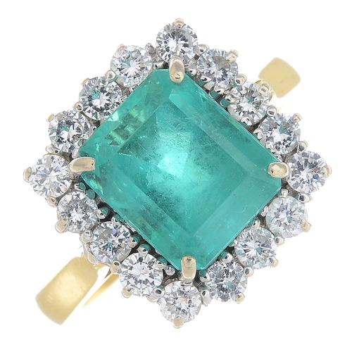 3 - An 18ct gold Colombian emerald and diamond cluster ring. The rectangular-shape emerald, with brillia...