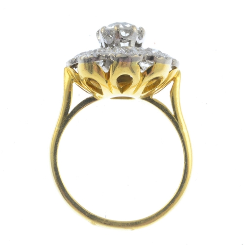 30 - An 18ct gold diamond cluster ring. The old-cut diamond, raised within a similarly-cut diamond scallo...