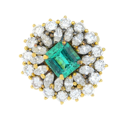 33 - An emerald and diamond cluster ring. The rectangular-shape emerald, with marquise-shape and brillian...