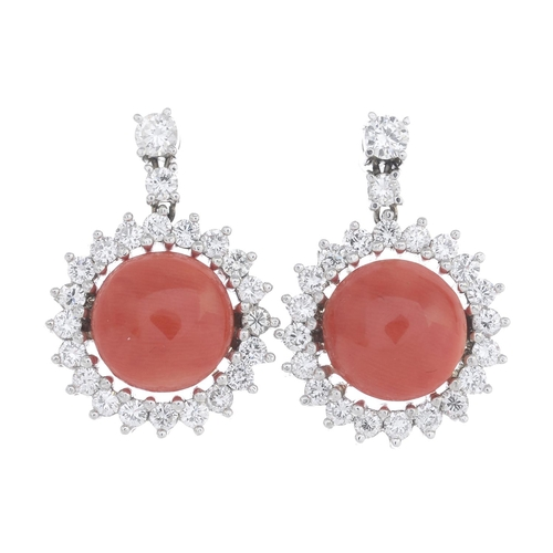 38 - A pair of coral and diamond cluster earrings. Each designed as a circular coral cabochon, with brill...