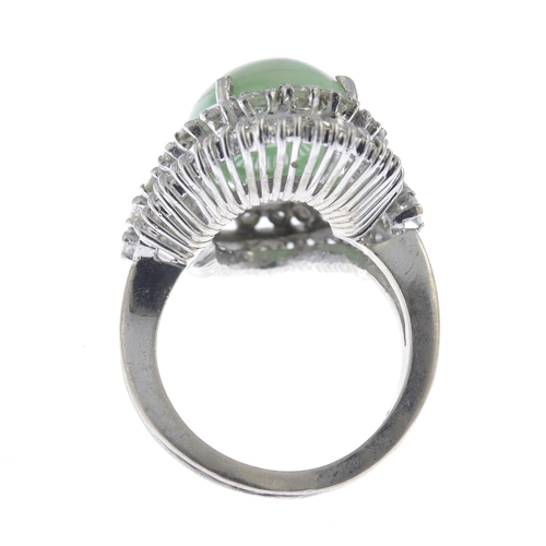 40 - A jade and diamond cluster ring. The oval jadeite cabochon, with brilliant-cut diamond scrolling sur...