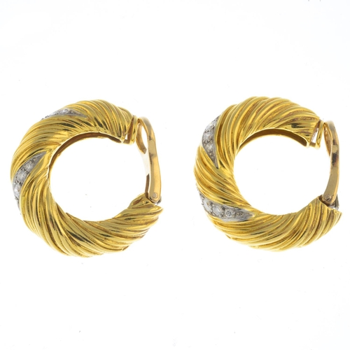 46 - KUTCHINSKY - a pair of 1970s 18ct gold diamond earrings. Each designed as a spiral-grooved hoop, wit...