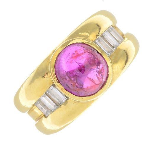 5 - A Burmese ruby and diamond ring. The oval ruby cabochon collet and graduated baguette-cut diamond li...