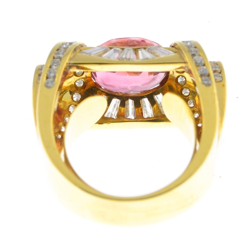 51 - A tourmaline and diamond dress ring. The oval-shape pink tourmaline, with tapered baguette-cut diamo...