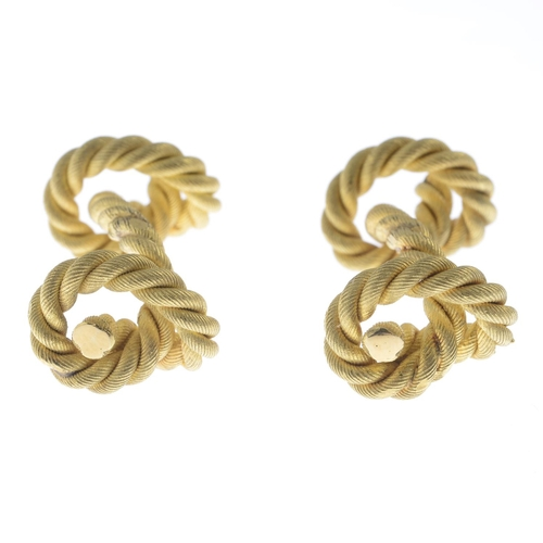 56 - HERMES - a pair of 18ct gold cufflinks. Each designed as a textured rope, knotted to the terminals. ...