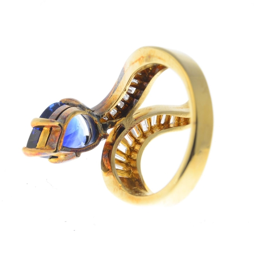 59 - A sapphire and diamond crossover ring. Designed as a stylised snake, the pear-shape sapphire head, t...