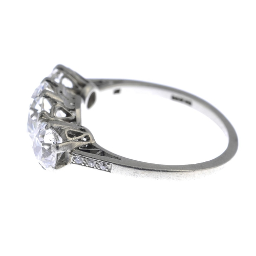 7 - A mid 20th century platinum diamond three-stone ring. The circular-cut diamond, with similarly-cut d...