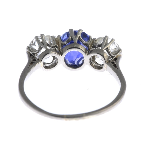 12 - An early 20th century 18ct gold and platinum, Sri Lankan sapphire and diamond three-stone ring. The ...