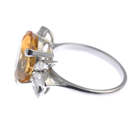 14 - A topaz and diamond cocktail ring. The oval-shape yellow topaz, with marquise-shape diamond trefoil ...