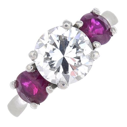 16 - A diamond and ruby three-stone ring. The brilliant-cut diamond, with circular-shape ruby sides. Esti...