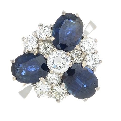 22 - A sapphire and diamond cluster ring. The brilliant-cut diamond, with oval-shape sapphire and similar...