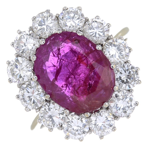 23 - A ruby and diamond cluster ring. The oval-shape ruby, with brilliant-cut diamond surround. Estimated...