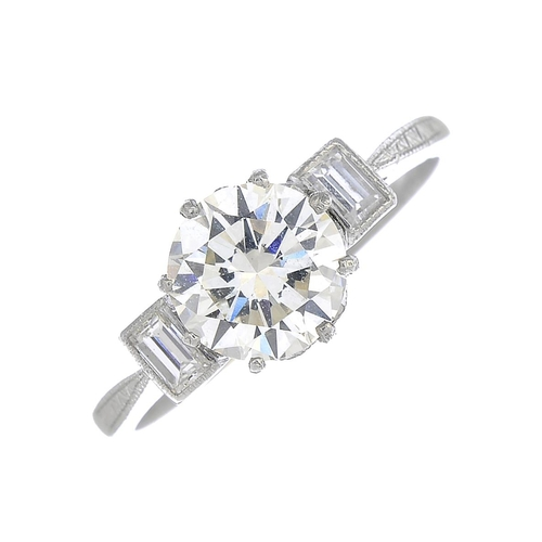 25 - A diamond single-stone ring. The old-cut diamond, with baguette-cut diamond sides and textured geome...