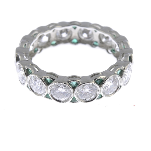 26 - A diamond and emerald full eternity ring. The brilliant-cut diamond collet line, with calibre-cut em...