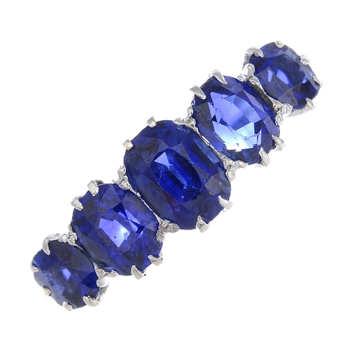 3 - An early 20th century platinum and gold, sapphire five-stone ring. The graduated cushion-shape sapph...