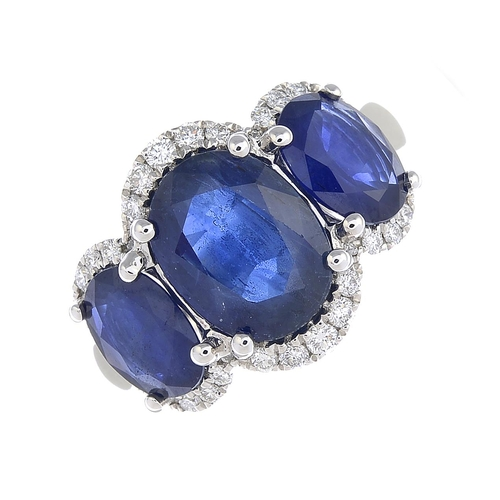 31 - A sapphire three-stone and diamond ring. The graduated oval-shape sapphire line, with brilliant-cut ...