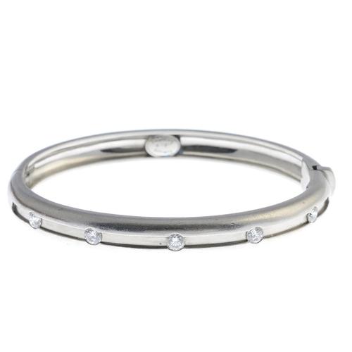 56 - BOODLES - a platinum diamond 'Amare' hinged bangle. Designed as five brilliant-cut diamonds, set at ...
