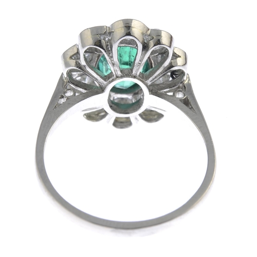 59 - An emerald and diamond floral cluster ring. The oval-shape emerald, with brilliant-cut diamond scall...