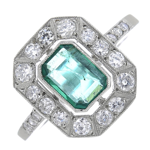 37 - An emerald and diamond cluster ring. The rectangular-shape emerald, with old-cut diamond surround an...