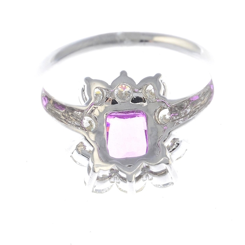 44 - A sapphire and diamond cluster ring. The cushion-shape pink sapphire, weighing 2.05cts, with brillia...