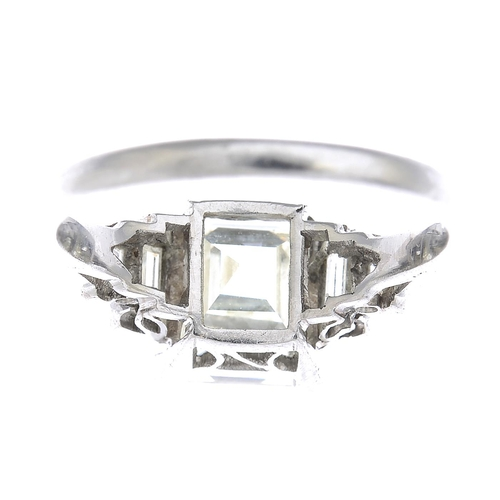 46 - A mid 20th century diamond single-stone ring. The square-shape diamond, with baguette-cut diamond st...