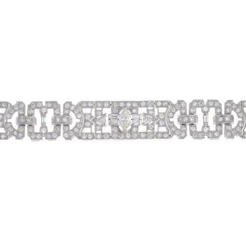 52 - A diamond bracelet. Of openwork design, comprising a series of pave-set diamond geometric panels and...