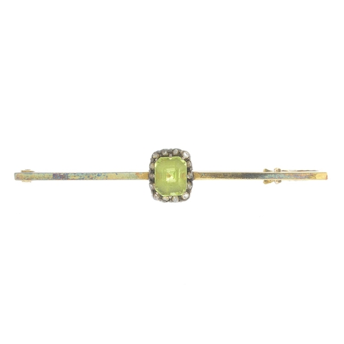 30 - An early 20th century silver and gold peridot and diamond bar brooch.Length 5.1cms. 2.7gms. With cas...