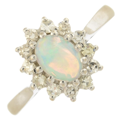 27 - An 18ct gold opal and diamond cluster ring.Approximate opal dimensions 7.1 by 5.8 by 2.4mms. Estimat...